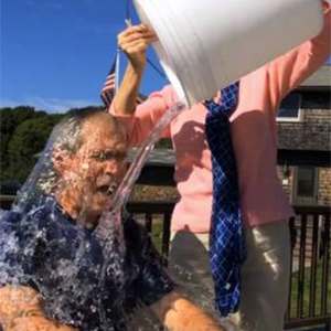 picture of a man having a bucket of water poured on his head, link opens new browser window
