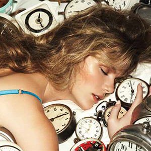 a picture of a woman lying on a bed of clocks, link loads PDF document in new browser window